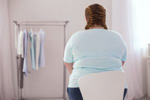 Obese woman sitting in a chair, looking at new clothes.