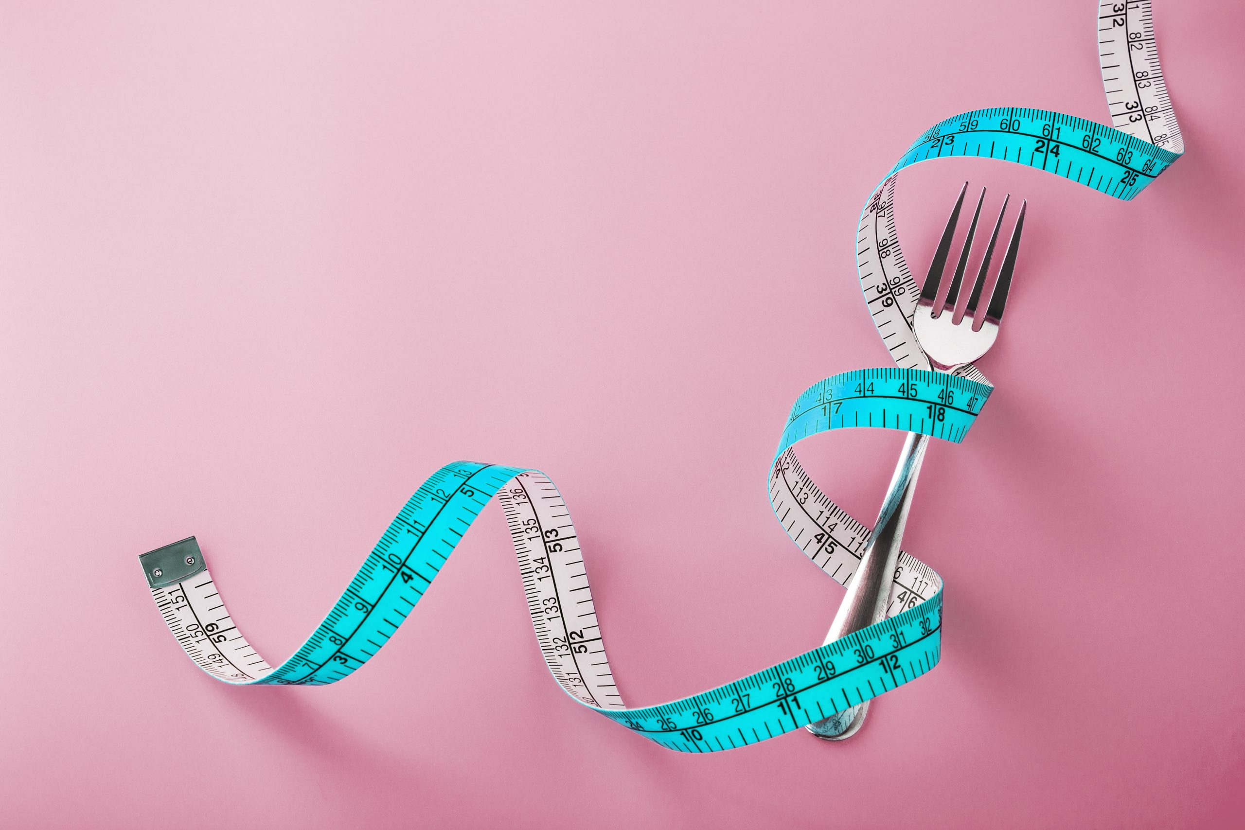 Fork with measuring tape around on pink background with space, diet concept
